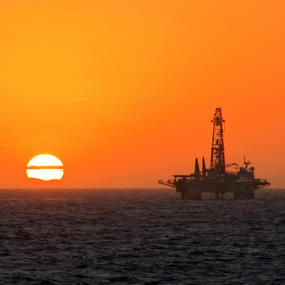 Oil rig at sea in sunset